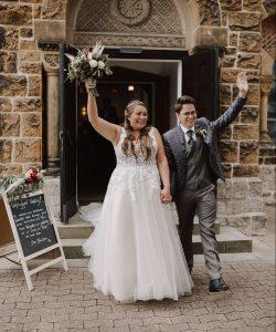 Brautpaar vor jubelt vor der Kirche