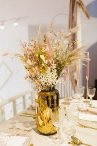 Goldene Vase mit Trockenblumenstrauss auf gedecktem Tisch