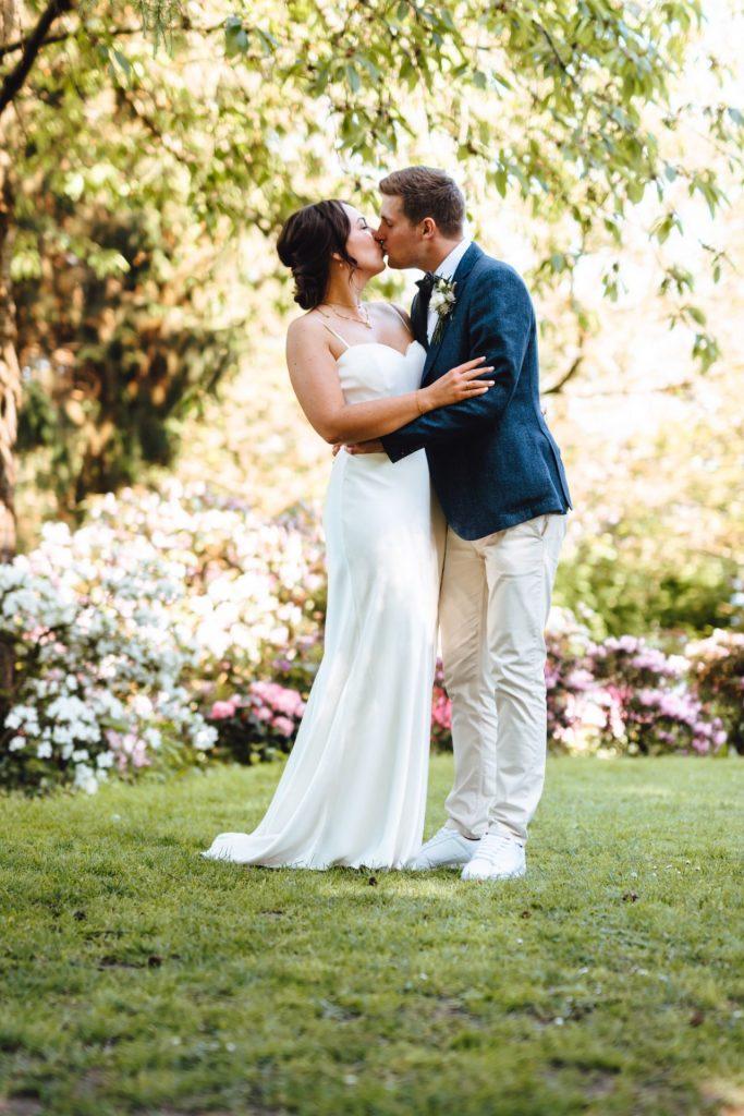 Brautpaar küsst sich unter einem Baum