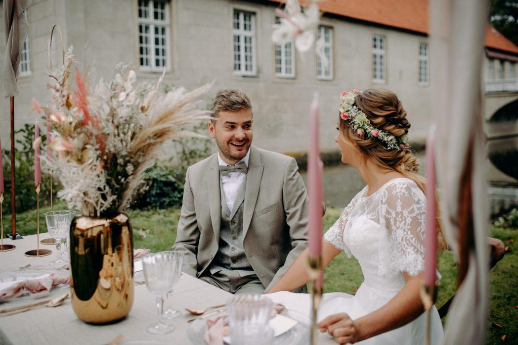 Hochzeitspaar sitzt an schön dekoriertem Tisch