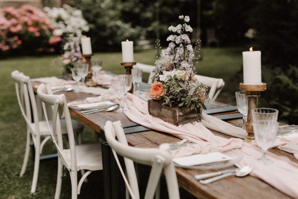 Dekorierter Holztisch mit Tischläufer, Blumen und Kerzen